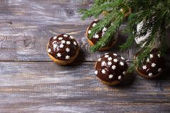 Spicy pumpkin muffins with nuts, decorated with chocolate glaze and sugar snowflakes under the Christmas tree on a wooden table royalty free stock photography