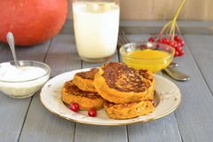 Spicy pumpkin pancakes with honey and sour cream. Homemade spicy pumpkin pancakes with honey and sour cream, fritters Stock Images