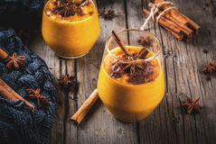Spicy pumpkin pie smoothie. Traditional autumn dishes, spicy pumpkin pie smoothie with cinnamon, anise and oatmeal. In portioned glasses, on rustic wooden old stock images