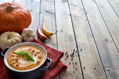 Spicy pumpkin soup with chili, pepper and garlic in a dark ceram Stock Photography