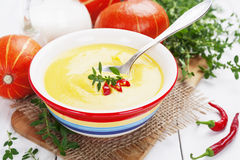 Spicy pumpkin soup with cream and chili pepper Stock Images