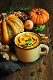 Spicy pumpkin soup with ginger and onion, served in a mug. Spicy pumpkin soup with ginger and onion served in a mug with pumpkin oil and croutons. Here is a stock image