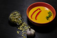 Spicy pumpkin soup on dark background stock photo