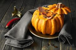 Spicy pumpkin soup served in a hollowed pumpkin on wood. Spicy pumpkin soup served on a dark wood  in a hollowed pumpkin with croutons, pumpkin oil and seeds Stock Image