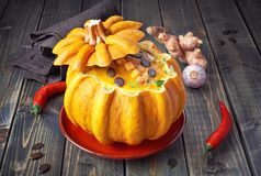 Spicy pumpkin soup served on a dark wood  in a hollowed pumpkin. With croutons, pumpkin seeds and thyme Royalty Free Stock Photos