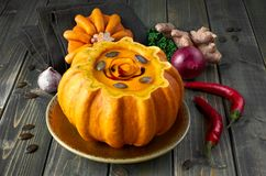 Spicy pumpkin soup served in a hollowed pumpkin on dark backgrou Royalty Free Stock Photos