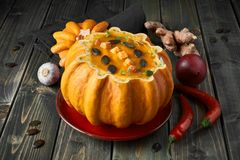 Spicy pumpkin soup served in a hollowed pumpkin on dark wood wit. Spicy pumpkin soup served in a hollowed pumpkin on dark wooden background. The soup was Stock Images