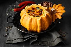 Spicy pumpkin soup served in a hollowed pumpkin on dark wooden b. Spicy pumpkin soup served in a hollowed pumpkin on dark wood and stone. The soup was seasoned Royalty Free Stock Image