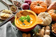 Spicy pumpkin soup served in a hollowed pumpkin with ingredients. Spicy pumpkin soup seasoned with ginger and garlic, served in a hollowed pumpkin with croutons Royalty Free Stock Photography
