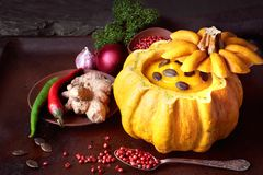 Spicy pumpkin soup served in a hollowed pumpin on dark backgroun. D. The soup was seasoned with chili, spanish onion, garlic, ginger, parsley and pink pepper Stock Photos