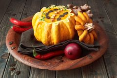 Spicy pumpkin soup served in a hollowed pumpkin on wood. Spicy pumpkin soup served in a hollowed pumpkin with croutons, thyme and pumpkin seeds on wood Stock Photo