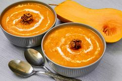 Spicy pumpkin soup with walnuts decorated with sliced yellow pumpkin on the gray concrete background. Traditional autumn food. Or thanksgiving dish. Close up stock photos