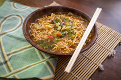 Spicy Ramen Noodle Soup. Spicy asian ramen noodle soup with chopsticks in wooden bowl Stock Photos