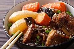 Spicy ribs stewed with mushrooms, pears and carrots close-up in royalty free stock images