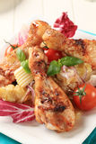 Spicy roast chicken drumsticks with potato salad Royalty Free Stock Images