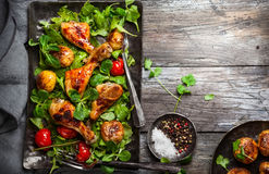 Spicy roasted chicken legs. With potatoes and salad. Top view. Food in rustic style Stock Photography