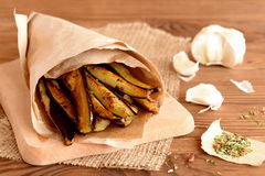 Spicy roasted eggplant in the wrapping paper on a burlap and cutting board. Spices, garlic on a wooden table. Deep fried eggplant recipe. Closeup Stock Photo