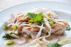 Spicy salad with fried fish and green herb in Thai Stock Images