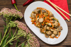 Spicy salad of mushrooms and carrots in Korean. Top view. Close-up. Wooden rustic background. Marinated mushrooms and carrots in Korean. Top view. Close-up stock photography