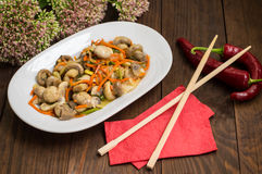 Spicy salad of mushrooms and carrots in Korean. Top view. Close-up. Wooden rustic background. Marinated mushrooms and carrots in Korean. Top view. Close-up stock images