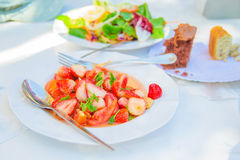 Spicy salad with strawberry , tomato and coriander. Food on white dish Stock Photo