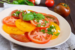 Spicy salad of yellow, red, black tomatoes, cut into circles with garlic and greens on a plate on a dark wooden background Stock Photos