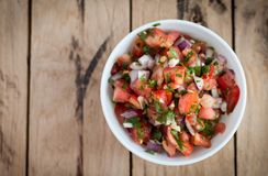 Spicy salsa dip in a bowl on wooden background, top view royalty free stock photos