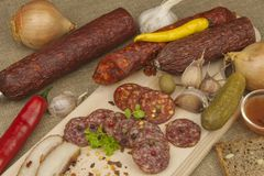 Spicy sausages on a wooden cutting board. Preparing the menu. Entertainment for visitors Royalty Free Stock Images