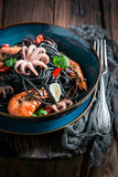 Spicy seafood black pasta made of octopus, tiger prawns Royalty Free Stock Photo