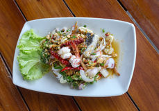 Spicy seafood salad in plate on the wood table Stock Photography