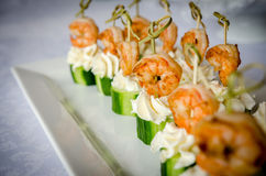 Canape with shrimp, cucumber and cream cheese. Spicy shrimp with cucumber and cream cheese skewers served on plate. Close up view Stock Photos