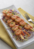 Spicy shrimp skewers on coleslaw salad. With yogurt cucumber dill dressing Stock Image