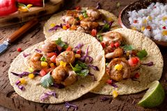 Spicy Shrimp Tacos. Delicious spicy shrimp tacos with sriracha mayo on a rustic wood table top royalty free stock images
