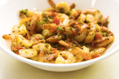 Spicy Shrimps. Delicious dish of sauted shrimp made with tomatoes, basil and select spices. Shallow DOF to highlight the shrimps in the foreground and eliminate stock image