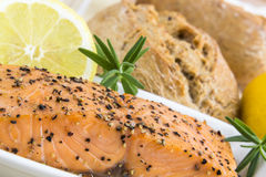 Spicy smoked salmon with lemon, rosmarin and bread bun Royalty Free Stock Photos