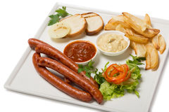 Spicy smoked sausage with cheese and fry potatoes in a pan. Stock Photography