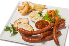 Spicy smoked sausage with cheese and fry potatoes in a pan. Royalty Free Stock Images