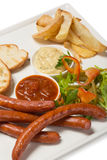 Spicy smoked sausage with cheese and fry potatoes in a pan. Stock Images