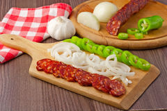 Spicy, smoked, sausage. Hungarian spicy, smoked, sausage. Served on a wooden plate wiht some fresh onion and green pepper Stock Photos