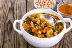 Spicy soup with chickpeas, pumpkin and curry in a white bowl on Royalty Free Stock Image