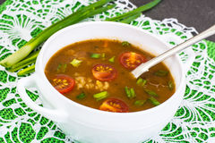 Spicy soup with curry, rice and grilled tomatoes Royalty Free Stock Images