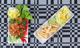 Spicy sour fried chicken salad with salad and french fires. Stock Image