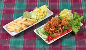 Spicy sour fried chicken salad with salad and french fires. Royalty Free Stock Image