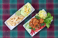 Spicy sour fried chicken salad with salad and french fires. Royalty Free Stock Photos