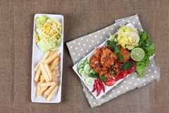 Spicy sour fried chicken salad with salad and french fires. Stock Photos