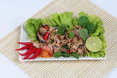 Spicy and sour mixed herb salad with pork and chicken on bamboo and white. Side view. Royalty Free Stock Images