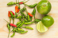 Spicy and Sour. Small chilli and lemon on wood chopping block Stock Images