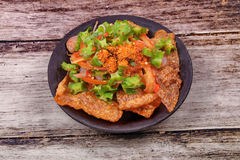 Spicy sour wing bean salad  with crispy pork served . Stock Photos