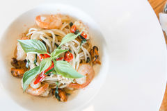 Spicy spaghetti seafood in white dish Stock Photo