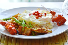 Spicy stir fried crispy pork curry with egg topping chili on rice. Spicy stir fried crispy pork curry with egg topping chili on plain rice Royalty Free Stock Photo